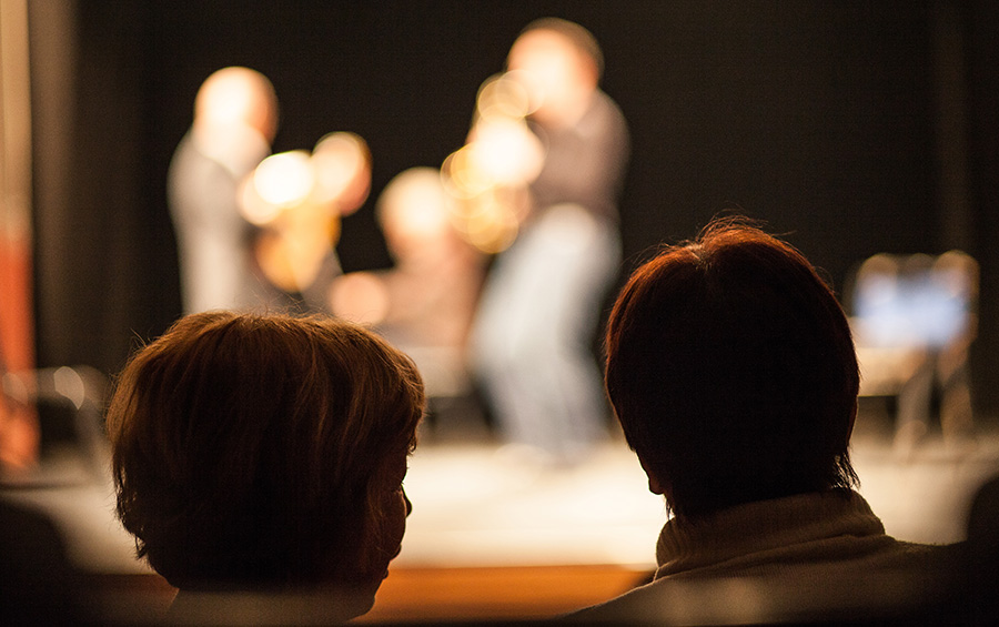 Silhouette of two women watching a live music show.