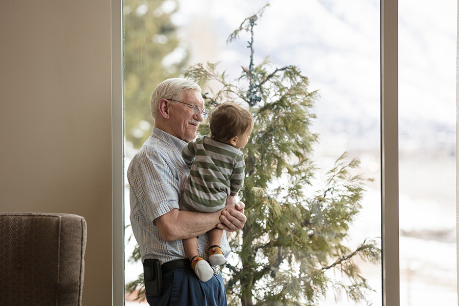 A senior citizen holding a grandchild while they look out a window at a snowy landscape.