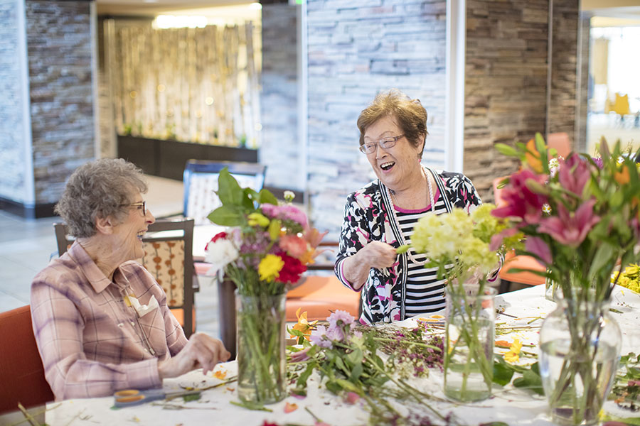 Two senior woman laughing while making floral arrangements