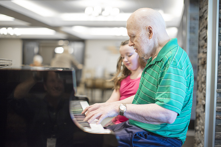 An elderly man teaching a young girl to play the piano.