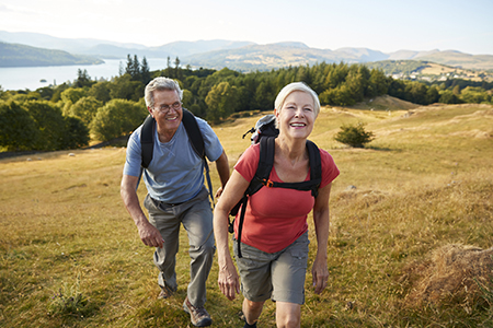 A couple, a senior man and senior woman, hike outdoors at a national park