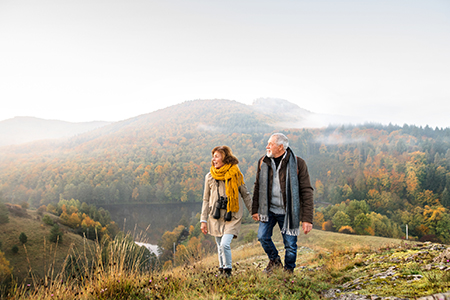 A senior woman and a senior man hold hands while walking through a national park in autumn
