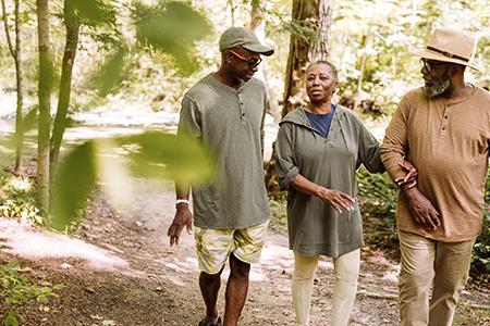 A senior couple walk through a national park with their son