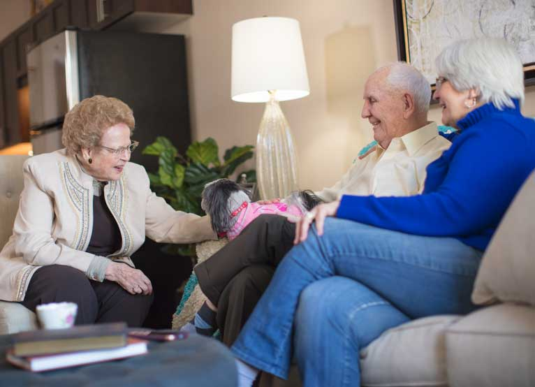 Three older adults sitting in a living room petting their dog.