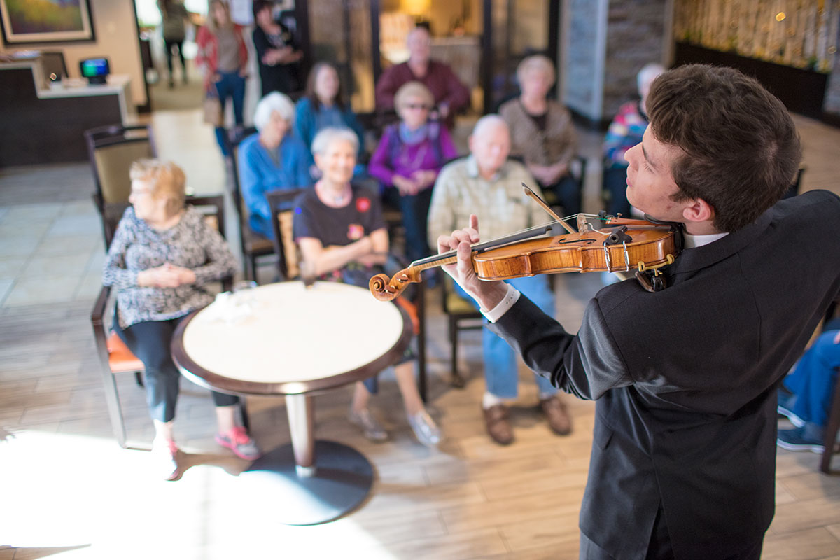 A violinist performing for a small group of seniors at a retirement home.