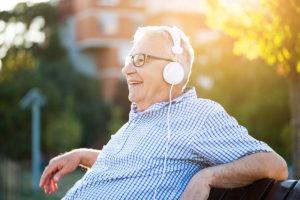 White senior elderly male with glasses listening to white over the ear headphones outside on a park bench