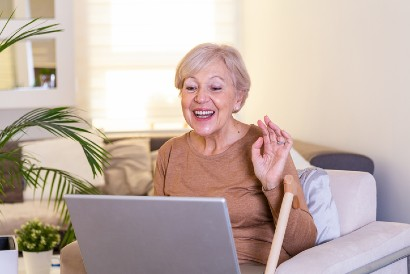 elderly woman video chatting loved ones on a laptop while sitting in a chair