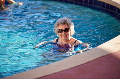 elderly woman smiling at the camera while swimming in a pool