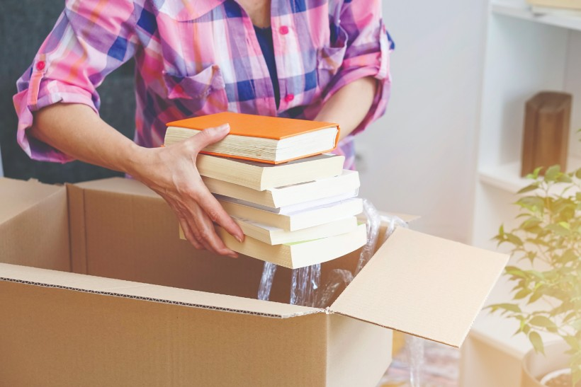 senior loading boxes with books to downsize to a retirement home