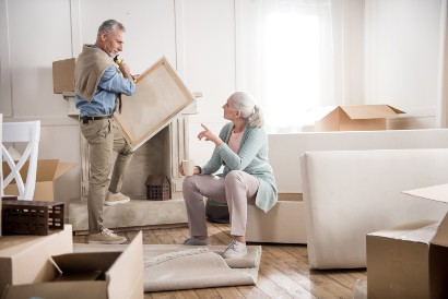 a senior couple packing to downsize to a retirement community
