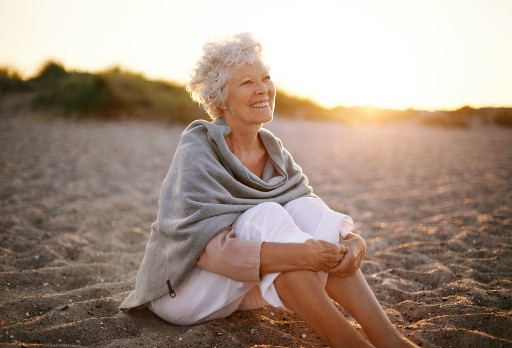 elderly woman sitting in the sand on a florida beach at sunset