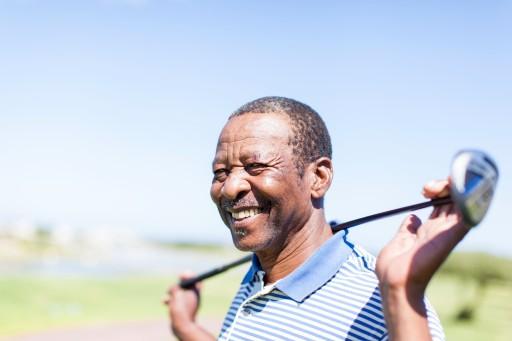 senior man golfing on a bright sunny day