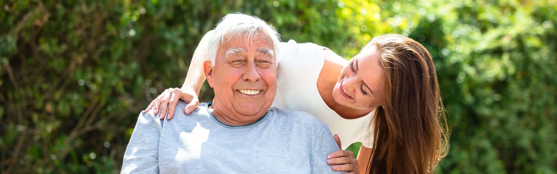 An elderly man smiling with his adult daughter