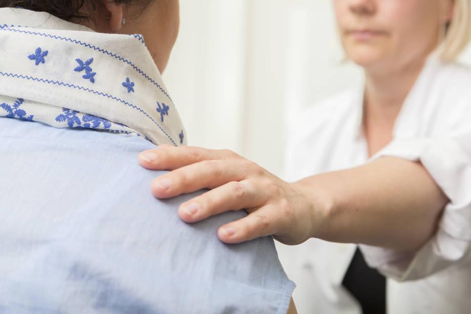 Lääkäri pitää kättään potilaan olkapäällä.
