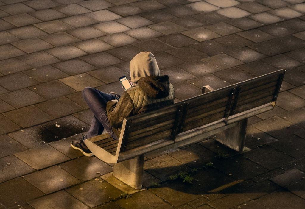 Mies istuu penkillä.