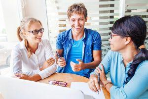 Kolme henkilöä keskustelevat pöydän äärellä