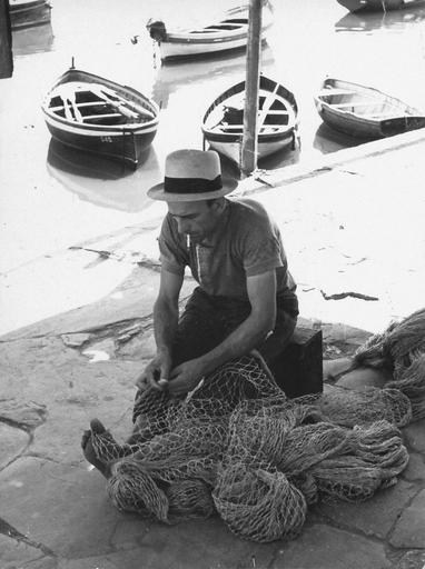 Un pescatore ripara la rete da pesca sul molo di Camogli (anni 1925-1950) / A fisherman in ...