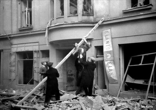 Finnish civilians rescue a woman from a bombed building during the first day of Soviet military ...