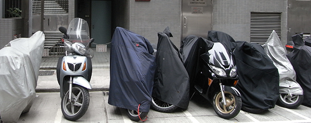 Motorbikes lined up with covers over