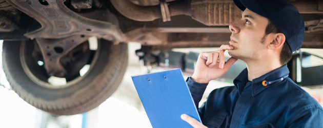 Man inspecting underside of car