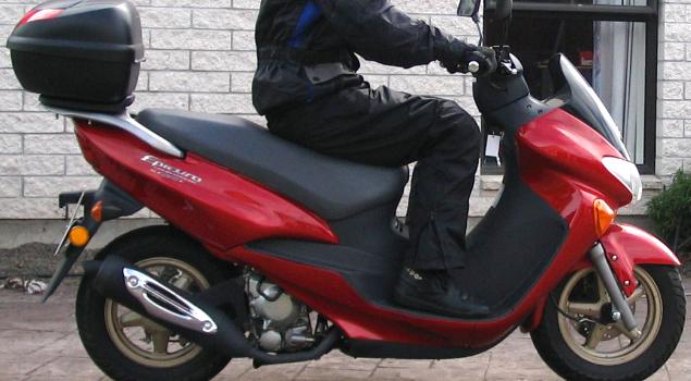 man_riding_red_suzuki_burgman