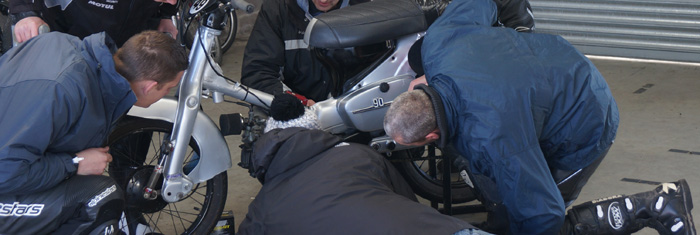 mechanics tinkering with a Honda C90