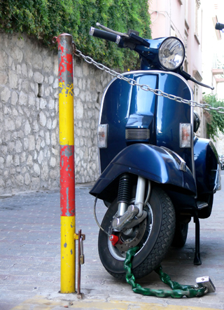 moped locked up against ground anchor in text image