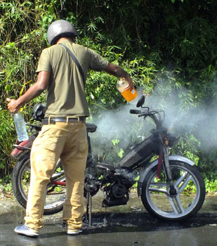 motorbike on fire being doused with water