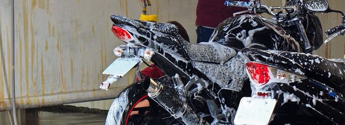 two motorbikes being washed in a garage