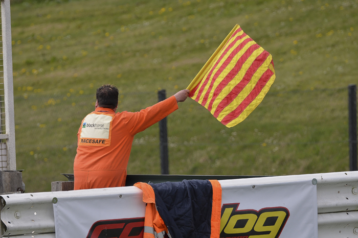 marshal waving red and white striped flag