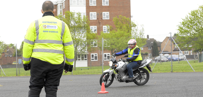 Learner rider manoeuvring around cones during a test