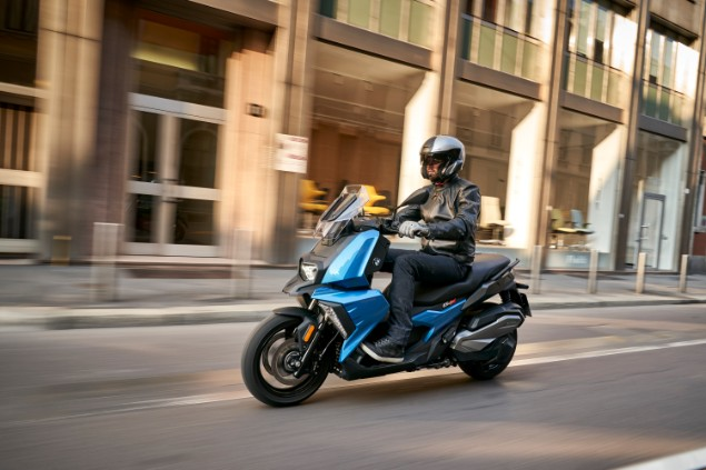 man-riding-a-BMW-C400X-down-the-road