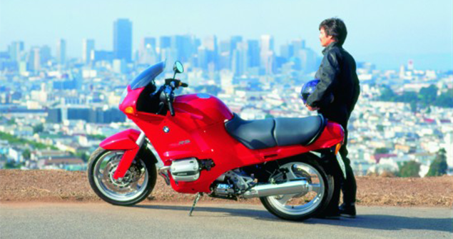 Male-standing-next-to-BMW-R1100RS-1992-with-city-background