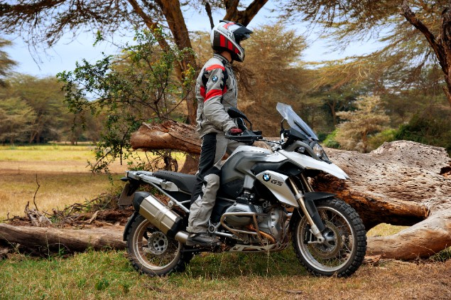 Motorcyclist-standing-up-on-BMW-R1100-RS-2012-next-to-tree