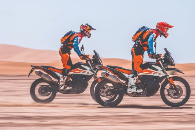 Two red KTM 790 Adventures riding together in action