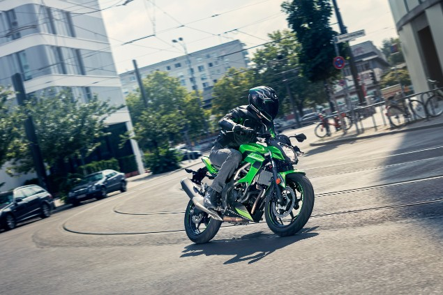 Green 2019 Z125 Kawasaki z125 motorcycle riding through town
