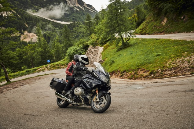Black BMW R1250RT motorcycle riding uphill on mountain