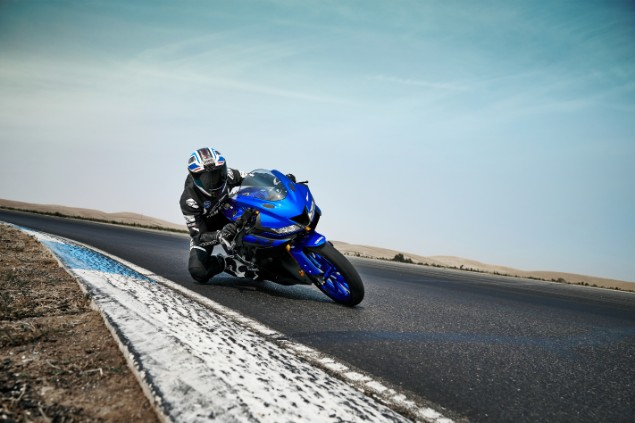 Blue 2019 Yamaha YZF R125 motorbike riding around racetrack corner