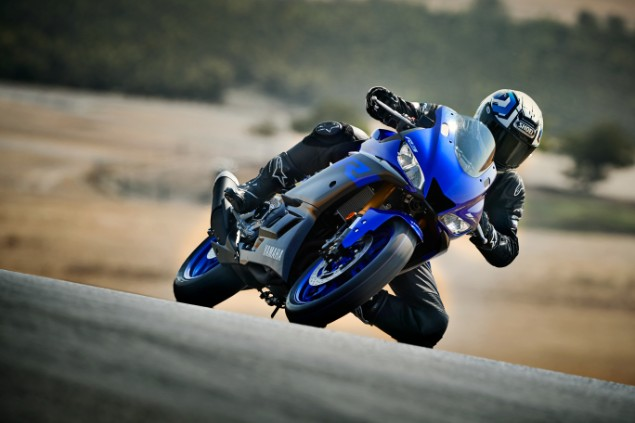 Blue 2019 Yamaha YZF-R3 motorcycle turning sharply around bend