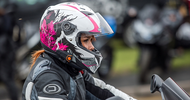 Female motorcyclist wearing custom pink rose helmet at the Worlds Largest Female biker meet 2018