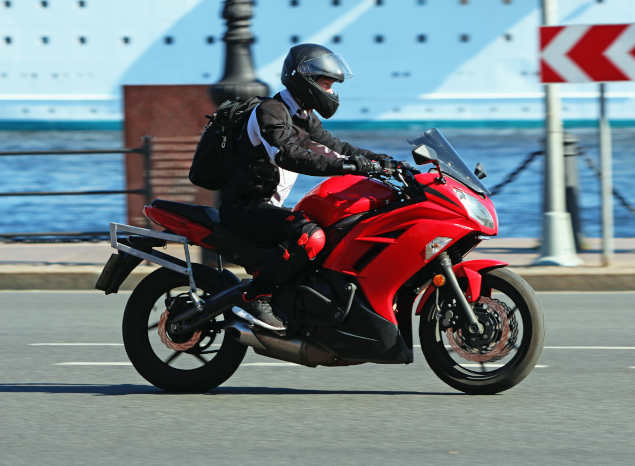 Motorcyclist riding red motorbike