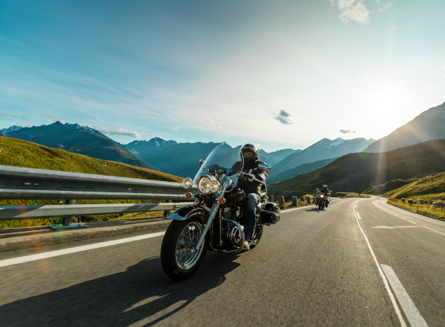 Two motorcyclists riding in european mountains
