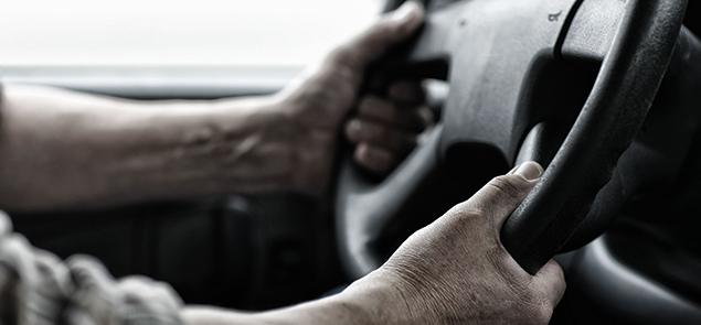Hands gripping steering wheel