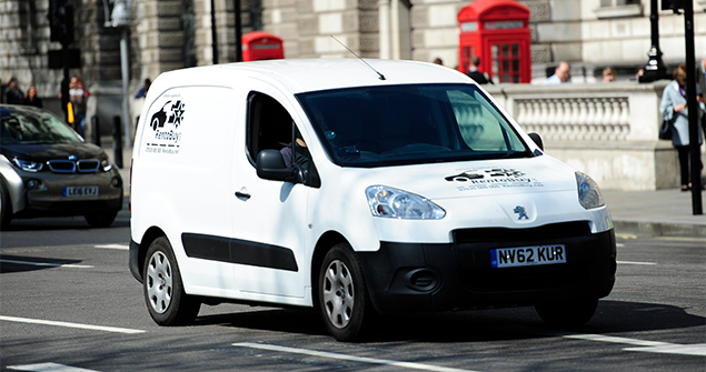 white-commercial-van-driving-on-road