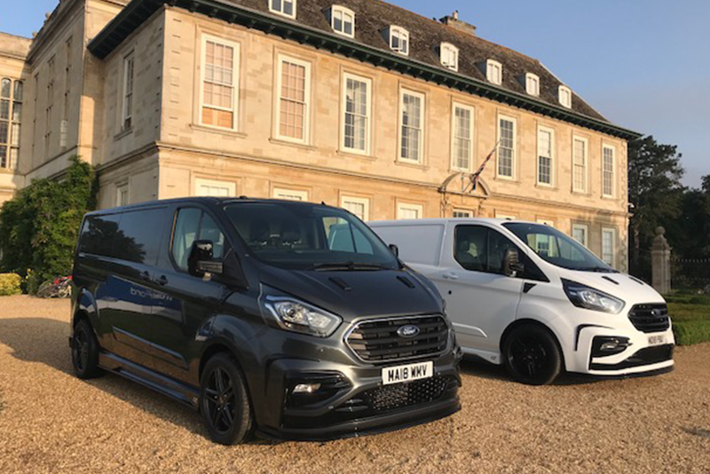 Two black and white TrustFord Transit GT vans stationary