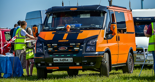 Orange ford transit mania with black striped vinyls parked on grass
