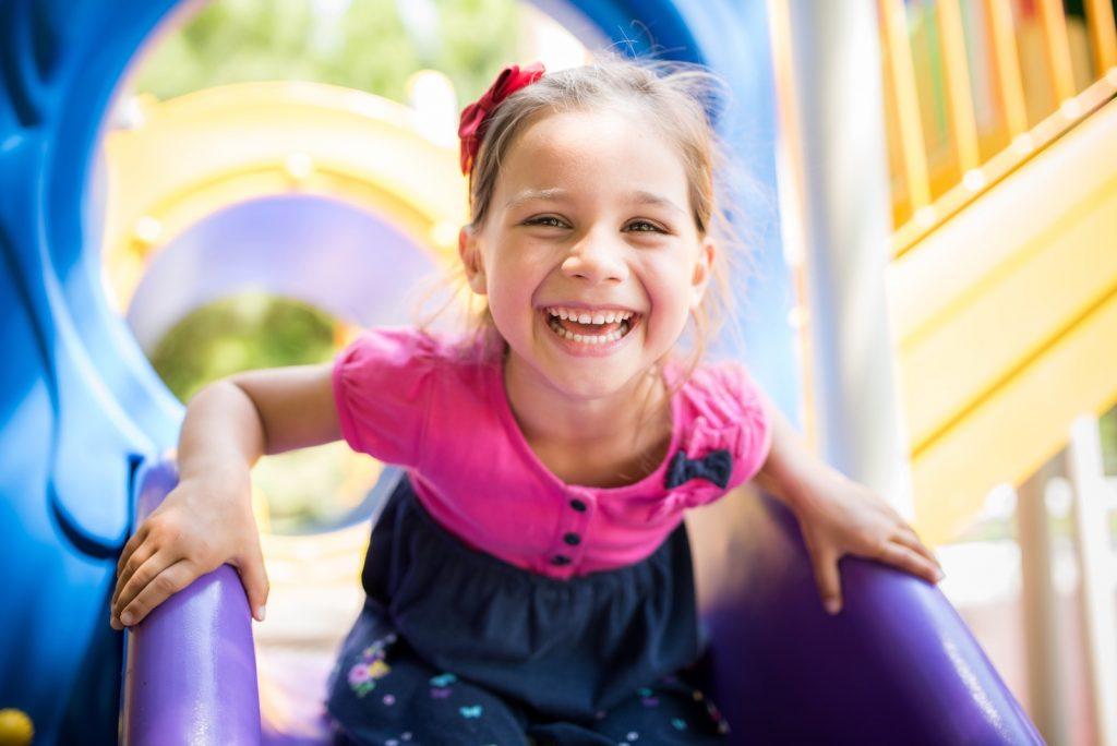 Smilende lita jente som leker på en lekeplass