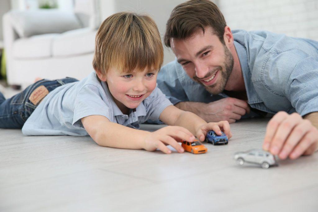 Liten gutt leker med biler samme med sin far