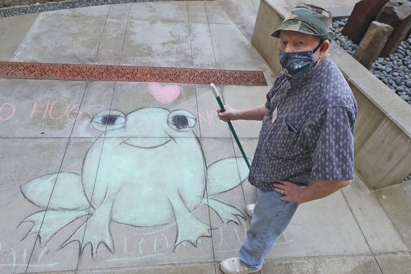 Timber Ridge resident in front of chalk drawing