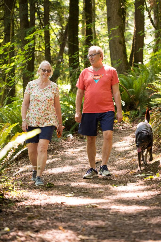 two seniors walk their dog
